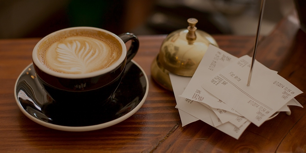 a cup of coffee and receipts